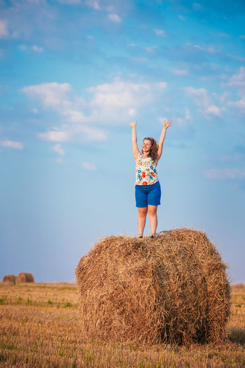 Beautiful Plus Size Young Woman Girl Is Standing On A Haystack With His Hands Up And Smiling. Sunset Of The Day In Summer Field Meadow Blonde Casual Hair Hands Haystack Inner Power Lady Standing Woman Young Attractive Beutiful  BIG Caucasian Cute Girl Model One People person Plus Size Portrait Pretty Smiling Weight Summer Exploratorium Be Brave This Is Strength International Women's Day 2019