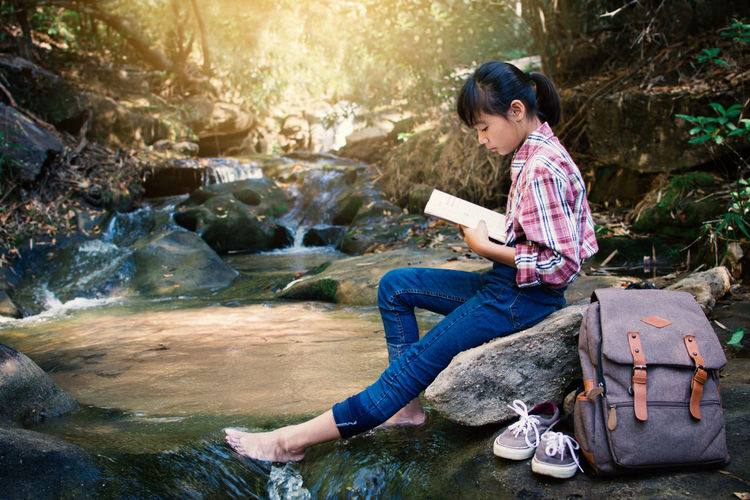 Girl reading book while sitting on rock at river