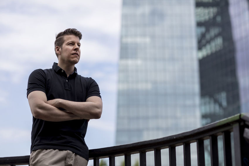 Man standing outside wearing casual clothing in front of a skyscraper in Germany. Low angle, looking away from camera. Adult Cloudy Khaki Pants Low Angle View Man Standing Arms Crossed Casual Clothing Caucasian Clouds Day Daylight Fit Glass Golf Shirt Handsome Looking Away From Camera Male Medium Shot Model Office Building Posing Rail Sky Skyscraper