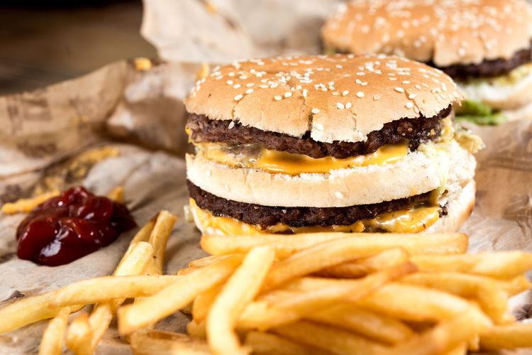Close-up of hamburger and french fries with ketchup on paper