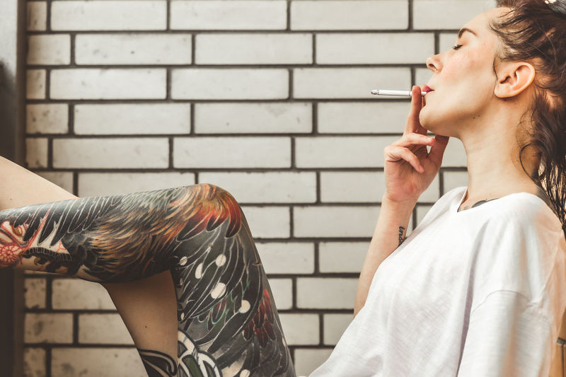 Side view of young woman smoking outdoors