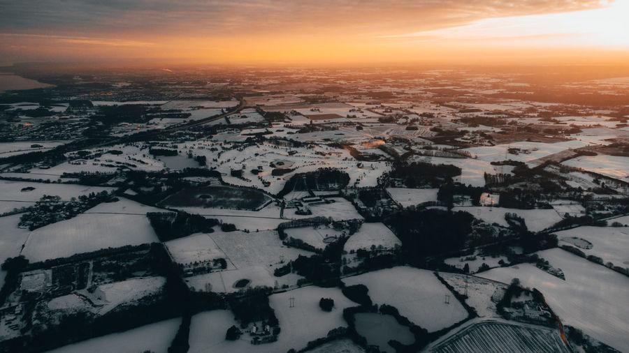 High angle view of snowcapped landscape against sky during sunset