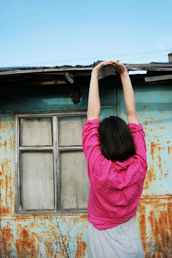 Built Structure Building Exterior Women Casual Clothing Lifestyles Females Girls Building Day Rear View Human Arm Arms Raised Leisure Activity Standing Facing Away Young Adult Window Old Buildings Rust Corrosion Colors Color Hairstyle Pink Color Real People One Person