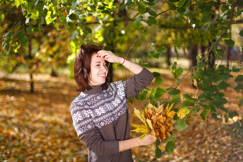 Happy caucasian young woman in a sweater holds bright autumn colors in her hand