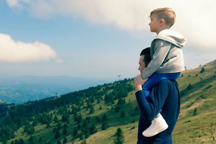 Father and son on mountain against sky