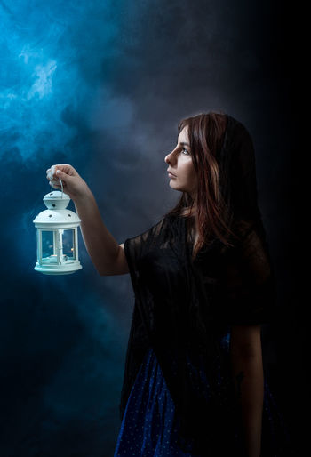 Woman Holding Lit Lantern While Standing By Wall