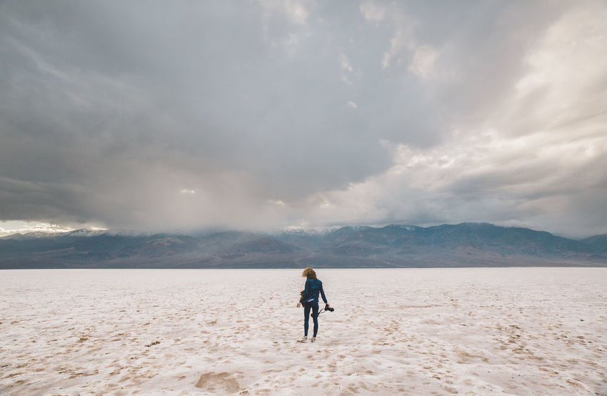Arid Climate Arid Landscape Bad Water Basin Beauty In Nature California Cloud - Sky Clouds Curly Hair Death Valley Death Valley National Park Desert Girl Landscape Mountains Nature One Person Outdoors Rear View Sand Scenics Sky Storm Tranquility Walking Weather