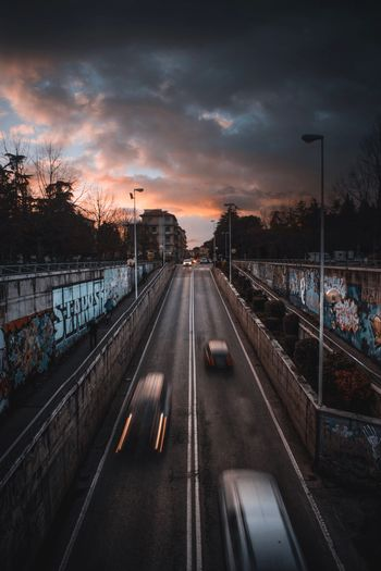 EyeEm Selects Sky Transportation Cloud - Sky Sunset The Way Forward Road Nature Direction Mode Of Transportation Street Diminishing Perspective Real People City vanishing point Incidental People Outdoors Plant Connection Car Tree