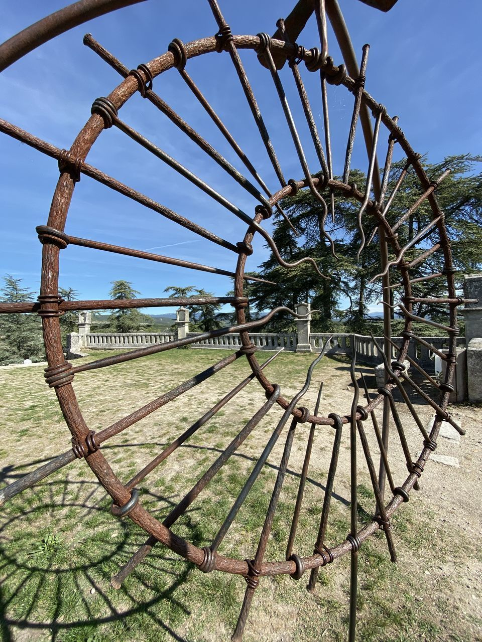 sky, day, nature, metal, tree, no people, plant, wheel, outdoors, rusty, land, shape, old, field, geometric shape, design, pattern, circle, built structure, barrier, spoke
