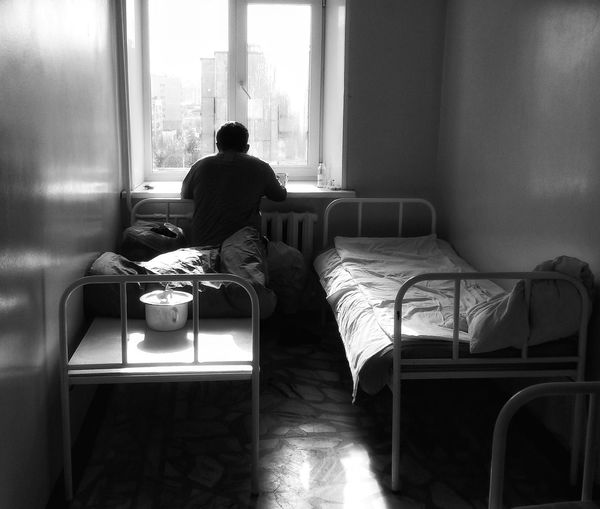 Rear View Of Man On Bed Looking Through Window In Hospital