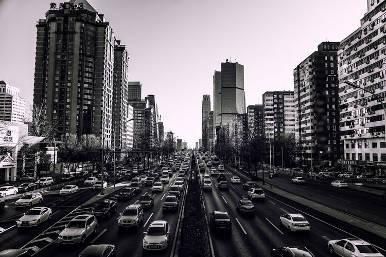 High angle view of traffic on road amidst modern buildings in city against clear sky