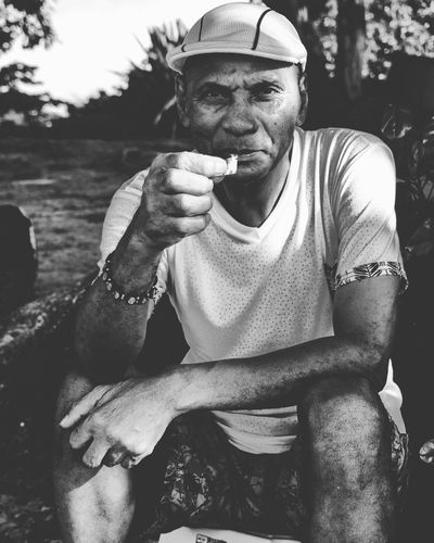 Portrait of man holding paper sitting outdoors
