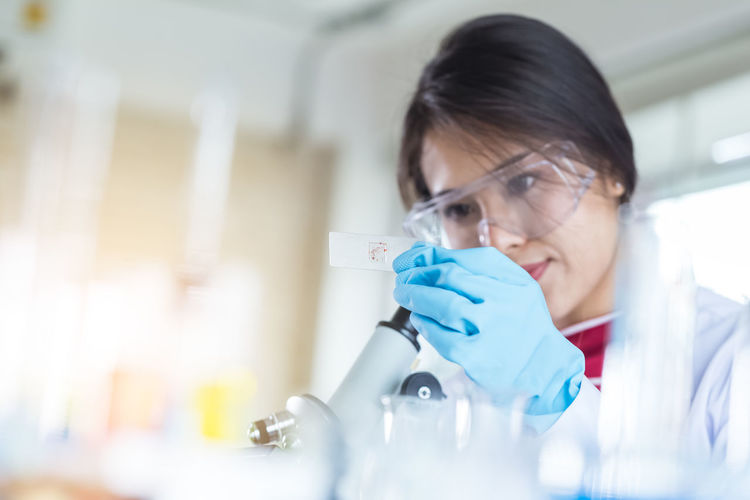 Close-up of scientist looking at sample on microscope slide