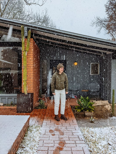 Portrait of woman standing in snow against building