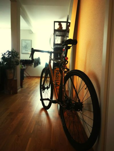 Bicycle parked on hardwood floor at home