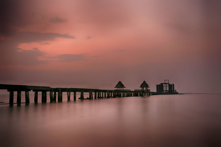 Old bridge in the sea on twilight time after sunset,nature of outdoor tropical coast in Thailand of Popular attractions the name is Wat Jit-ta-pha-wan in Chonburi province. Sky Water Sunset Architecture Built Structure Sea Scenics - Nature Cloud - Sky Waterfront Beauty In Nature Tranquility Tranquil Scene Nature No People Pier Orange Color Building Exterior Reflection Dusk Outdoors Wooden Post Old Bridge Old Bridge Abandoned Bridge Old Bridges Old Bridge Arch