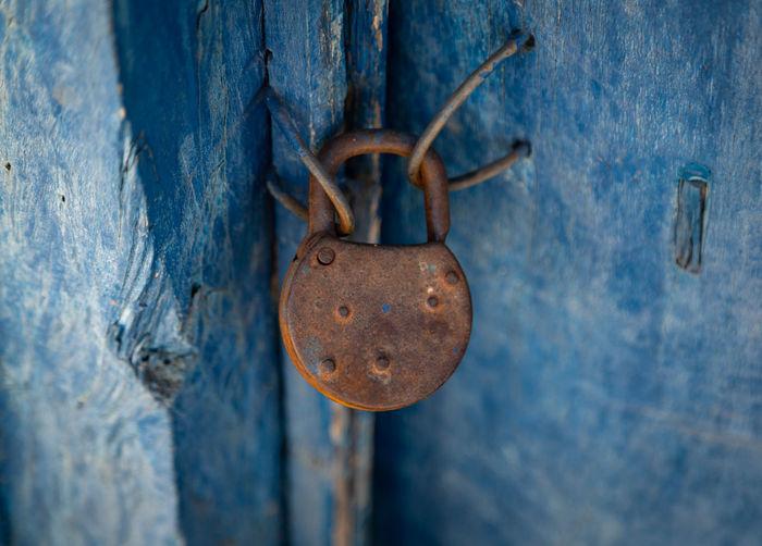 Close-up of rusty padlock hanging on wooden door
