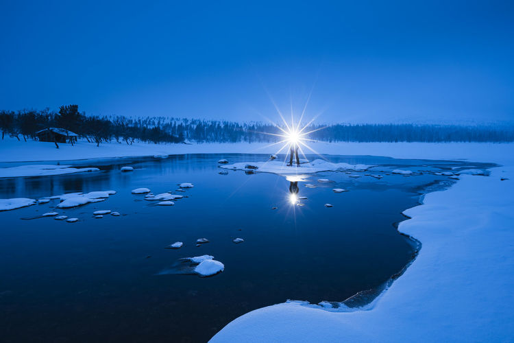 Scenic view of frozen lake against blue sky