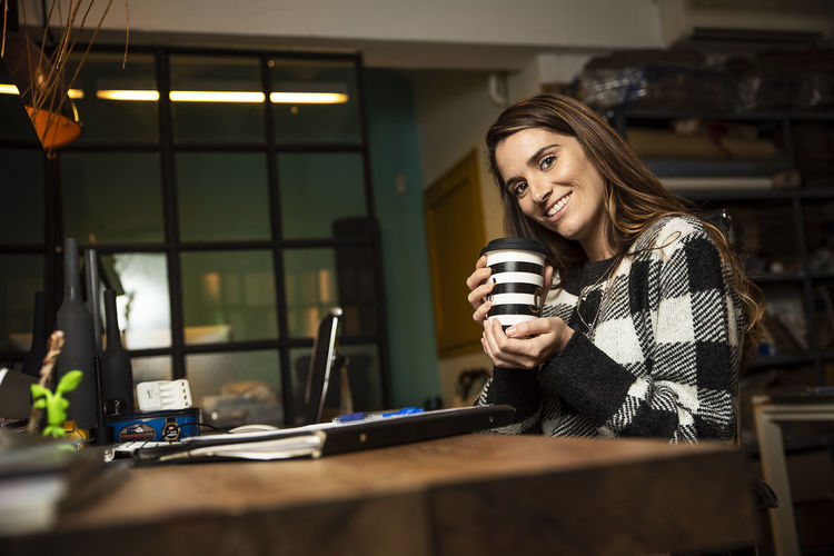 Portrait of smiling businesswoman holding disposable cup sitting at office