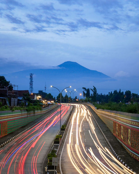 Light trails on road against sky in city