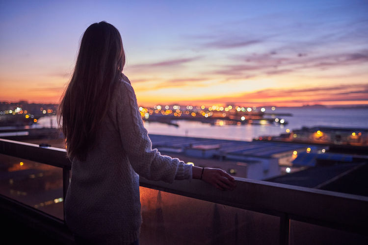 Rear view of woman looking at cityscape against sky during sunset