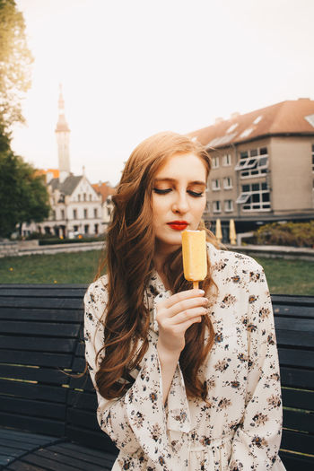 Young woman holding popsicle while sitting on bench
