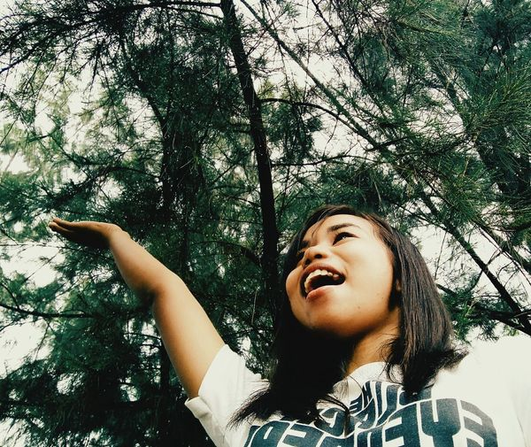 Low angle portrait of happy young woman in forest