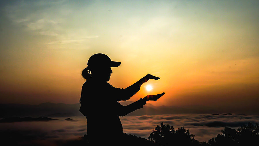 Silhouette man with arms outstretched against sunset sky