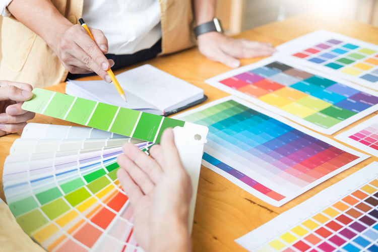 Colleagues discussing over color swatch at desk in office