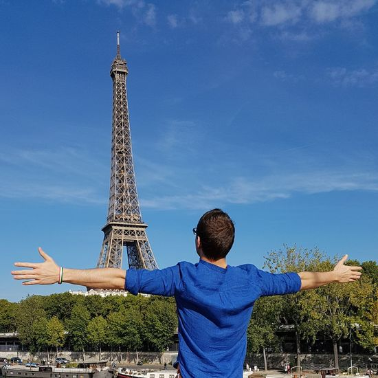 Rear view of man standing in front of eiffel tower against blue sky