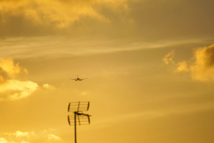 Low angle view of silhouette airplane flying against sky during sunset