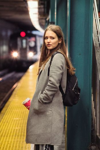 Beautiful young woman standing at subway station platform