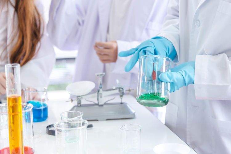 Midsection of scientists performing scientific experiment