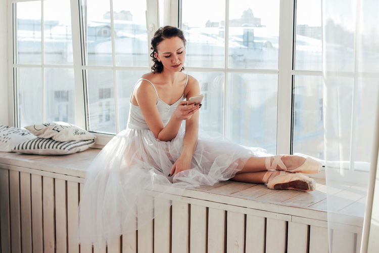 Ballet dancer using mobile phone while sitting at window
