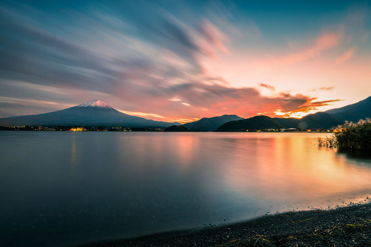 Mt. Fuji over Lake Kawaguchiko at sunset in Fujikawaguchiko, Japan. Water Sky Beauty In Nature Mountain Scenics - Nature Tranquil Scene Tranquility Cloud - Sky Lake Sunset Reflection No People Nature Idyllic Non-urban Scene Mountain Range Waterfront Mountain Peak Fujikawaguchiko Japan  Peak