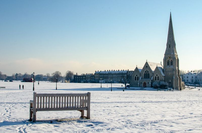 Empty bench on snow covered field with church in background against sky