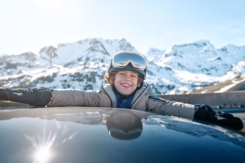 Portrait of smiling woman on snowcapped mountain