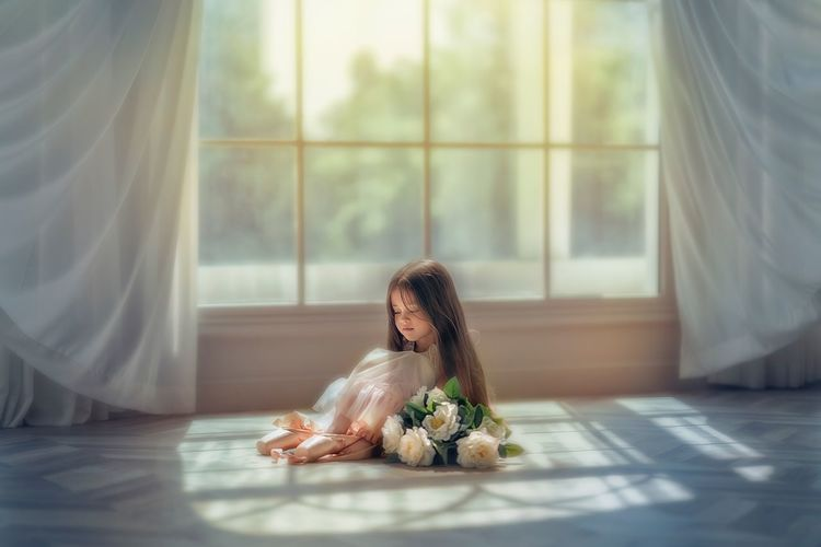 Full length of cute girl with flowers sitting on floor by window at home