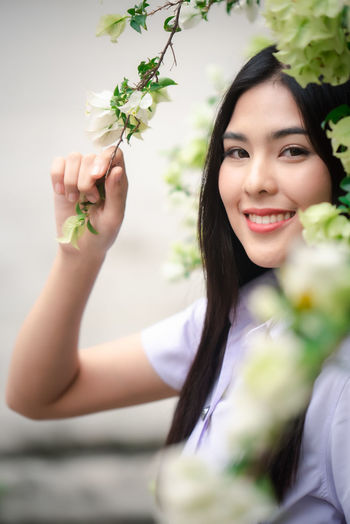 Portrait of a smiling young woman holding flower bouquet