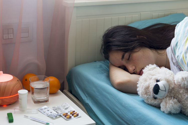 The young girl has a cold, lies in bed at home, feels unwell, takes medicines and vitamins, sleeps with a toy bear. Real People Sick Sickness Flu Feeling Indoors  Bed Relaxation Teddy Bear Teenager Teenage Girls Cold Wintertime Medicine Medical Supplies Sleeping In Bed Bedroom Fever Care Ill Illness Lying Down Domestic Room Headache