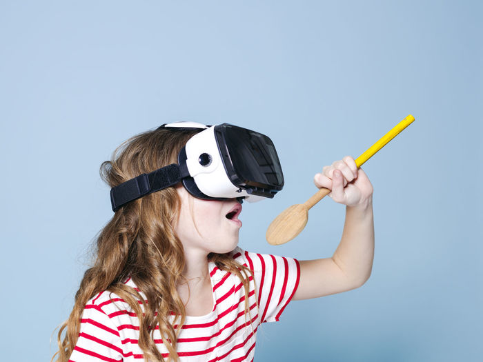 cool and smiling positive girl wearing virtual reality glasses goggles headset is singing with cooking spoon, new generation, concept in front of blue background Headshot Indoors  Child Portrait Studio Shot Childhood Striped Women Colored Background Girls Blue Background Holding Blue One Person Fun Copy Space Front View Leisure Activity Fashion Hairstyle Innocence 3-d Glasses Eyewear 3D Virtual Cooking Spoon Goggles Girl