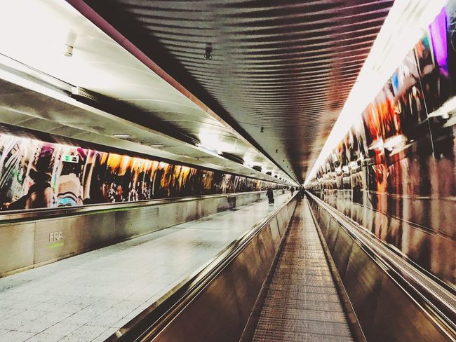 Illuminated Transportation Indoors  Architecture The Way Forward Ceiling Built Structure Real People Public Transportation Modern Moving Walkway  Tunnel Large Group Of People Day Indoors  Modern Transfer Airport Terminal Airport Pattern Low Angle View Traveling Architecture