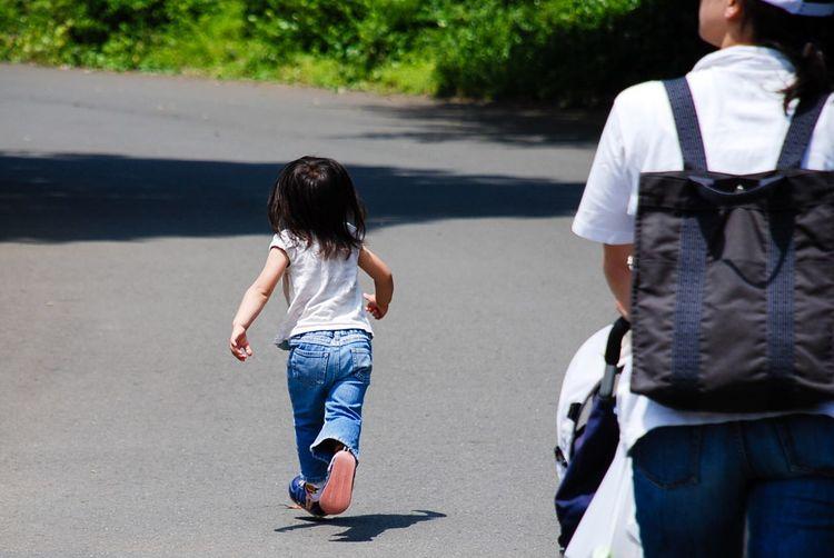 Rear View Of Girl Running On Street