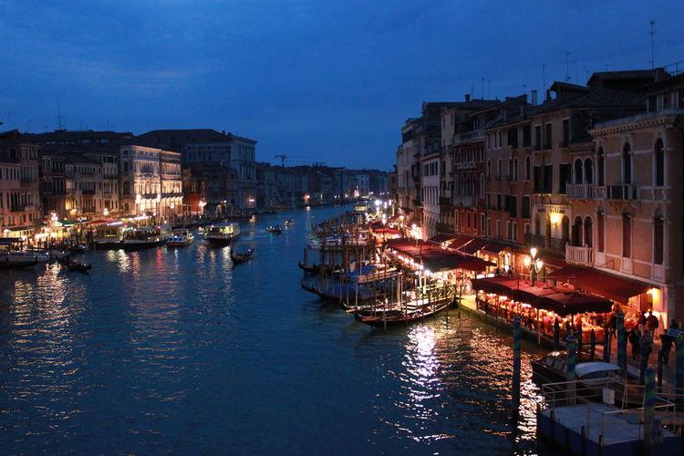Gondolas in grand canal amidst buildings against sky at dusk