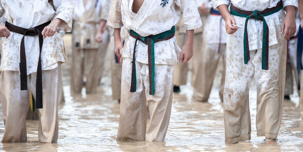 Midsection of people wearing karate belts standing in water
