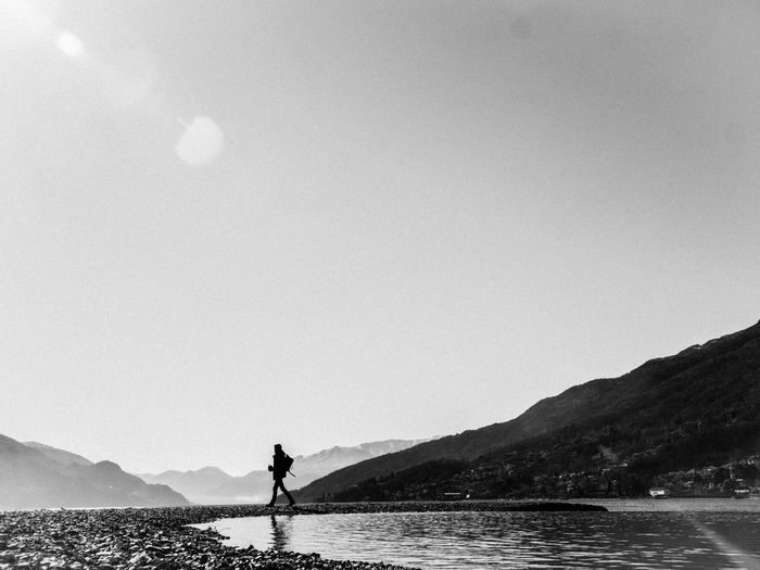Man standing on mountain by sea against clear sky