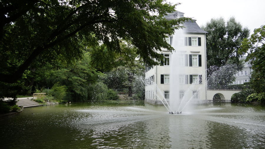 Tree Water Plant Architecture Building Exterior Built Structure Nature Waterfront Building No People Day Growth Motion Lake House Beauty In Nature Outdoors Fountain Residential District Spraying Flowing Water Flowing Popular Places