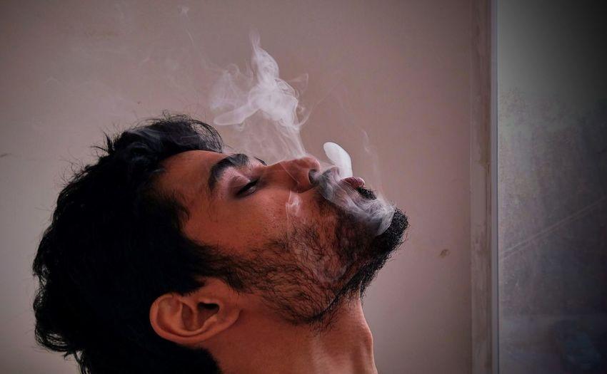 Man exhaling smoke at home