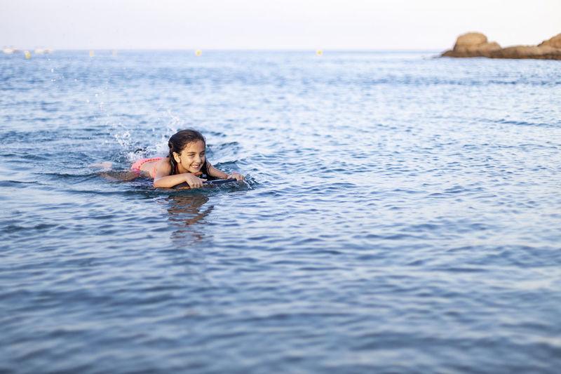 Cute girl swimming in sea against sky
