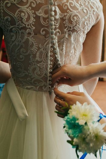 Cropped hands buttoning wedding dress of bride